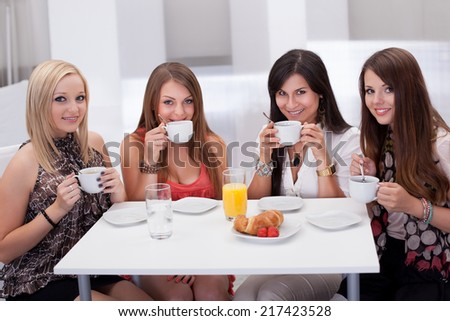 Four stylish attractive young female friends seated at a table chatting over coffee - stock photo