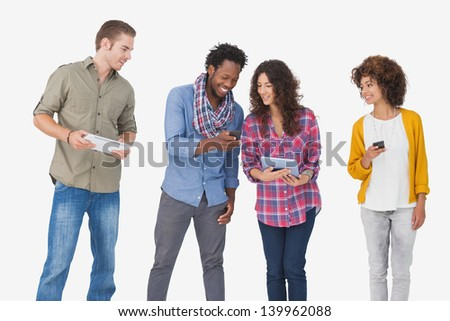 Four stylish friends looking at tablet and holding phones on white background - stock photo