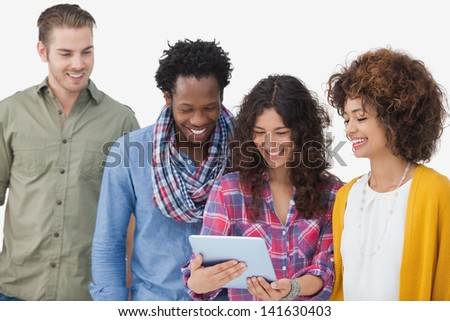 Four stylish friends looking at tablet on white background