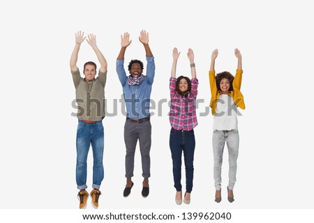 Four stylish friends smiling at the camera and jumping on white background