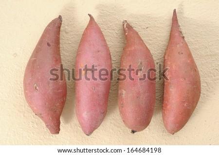 four  sweet potatoes  on yellow table - stock photo