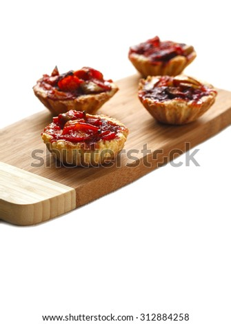 Four Tarts with apples on a cutting board on a white wooden table. isolated.