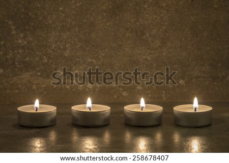 four tea candles on gray concrete background