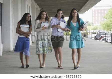 Four teenage girls holding books and hanging out in the school campus