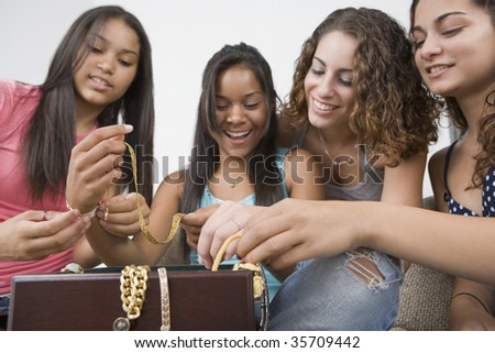 Four teenage girls holding jewelry and smiling
