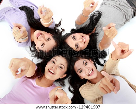 four teenage girls lying on the floor pointing at camera