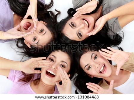 four teenage girls lying on the floor screaming - stock photo
