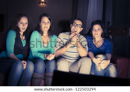 four teenager watching television on a sofa