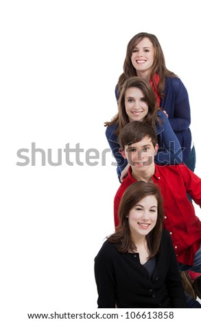 Four teenagers smiling on a white background with copy space - stock photo