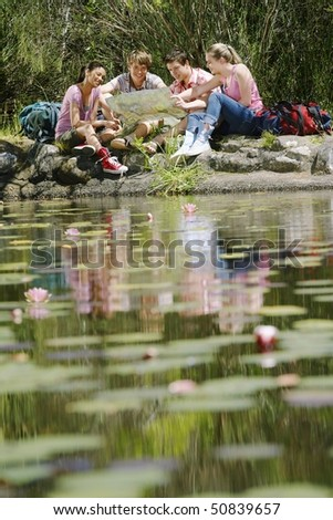 Four teenagers (16-217 years) sitting by lake, reading map, selective focus - stock photo
