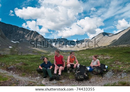 Four tired backpackers a family resting in mountains - stock photo