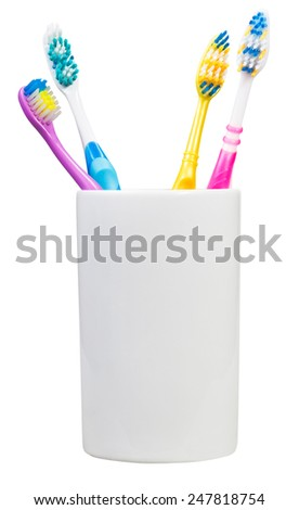 four tooth brushes in ceramic glass - family set of toothbrushes isolated on white background - stock photo