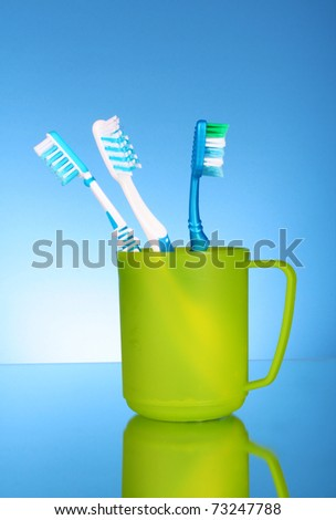 Four toothbrushes in plastic cup on blue background