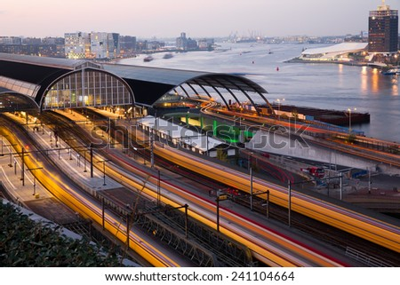 Four trains coming in Amsterdam Central Station at dusk, the golden hour, leaving light trails with the Amstel river and the city in the background, in Amsterdam, capital of the Netherlands - stock photo