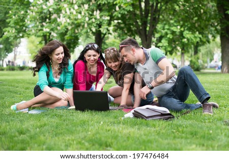 Four university students comparing their notes from college, sitting in the park on a beautiful day - stock photo