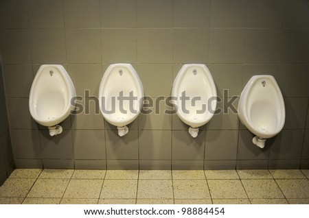 Four Urinal In The Bathroom With Grey Walls