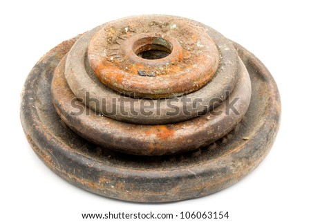 Four various sized, un-used, rusty and dusty weights stacked on top of each other. - stock photo