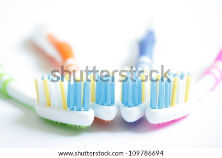 Four very colorful toothbrushes on a white background. - stock photo