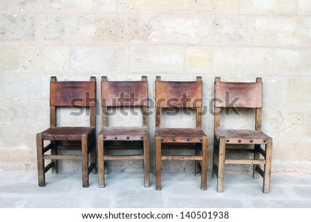 four vintage chairs at the stone wall - stock photo