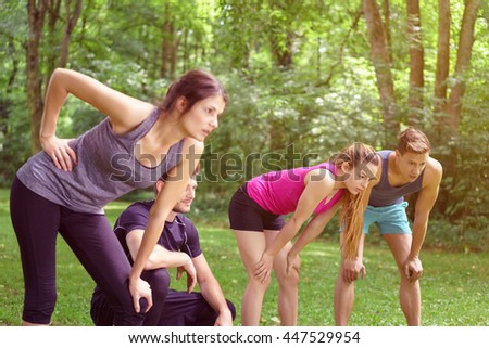 Four weary friends resting after working out in a park leaning forwards on their knees in their sportswear in a healthy lifestyle concept - stock photo