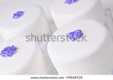 four wedding cakes with purple flowers - stock photo