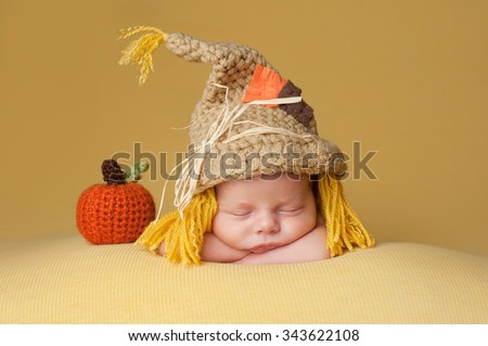 Four week old newborn baby boy wearing a crocheted scarecrow hat. He is sleeping on a gold blanket next to a crocheted pumpkin. - stock photo