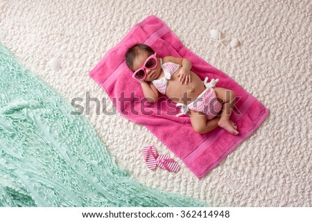Four week old newborn baby girl sleeping on a pink towel. She is wearing a crocheted pink and white bikini and pink sunglasses. Shot in the studio with props made to look as if she's at a beach. - stock photo