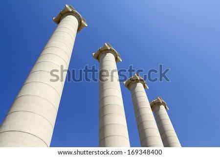 Four white columns near Royal palace. The columns, symbolizing the four stripes of the Catalan flag - stock photo