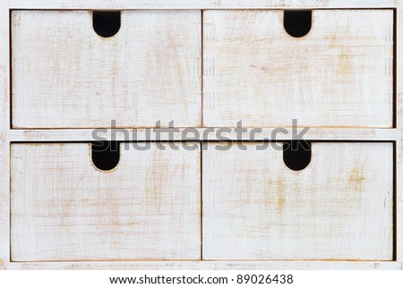 Four white wooden drawers with black holes - stock photo