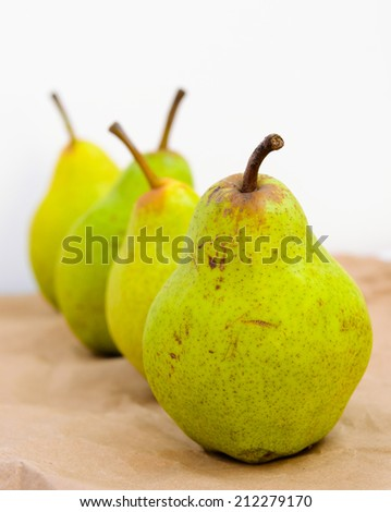 Four Williams Pears on brown paper - stock photo