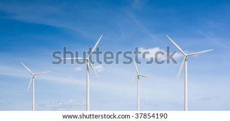 Four wind turbines on a cloudy blue sky.