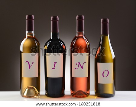 Four Wine Bottles with their labels spelling out the word VINO, on a light to dark gray background. Wines include: Cabernet Sauvignon, Chardonnay, Sauvignon Blanc, and White Zinfandel. - stock photo