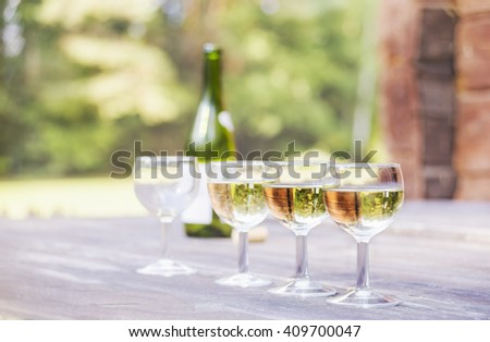 Four wineglasses and a wine bottle on a table