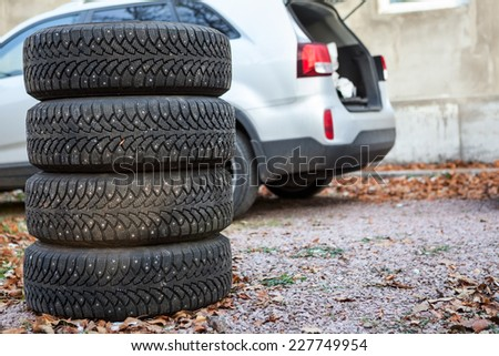 Four winter tire wheels are near suv, copyspace - stock photo