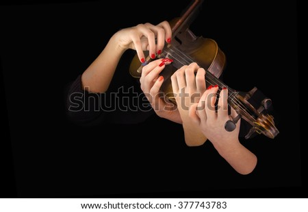 Four woman's hands playing the violin in a black background