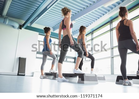 Four women at aerobics in gym - stock photo