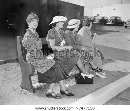 Four women sitting on a bench waiting for the bus - stock photo