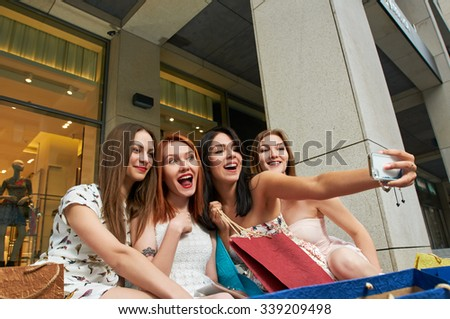 four women taking a selfie while shopping about clothing store. They are happy and smiling at camera phone. Shopping concept. - stock photo