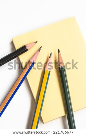 Four wood pencils and yellow paper note on white background