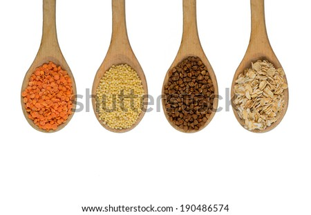 four wooden spoons with oats, grosbeak, buckwheat and millet on isolated background