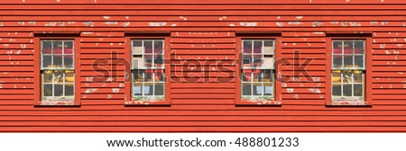 Four wooden windows on a red wall
