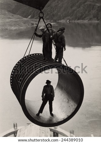 Four workers riding on a large casing section of pipe suspended from cable as it is moved into position during construction (1933-42) of the Grand Coulee Dam, Washington. - stock photo