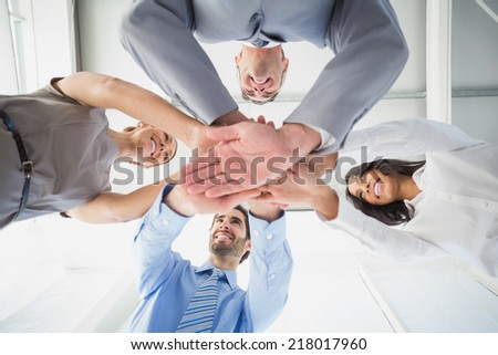 Four workers stacking hands together down to the camera