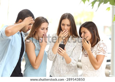 Four worried multi ethnic friends watching a smart phone in the street - stock photo