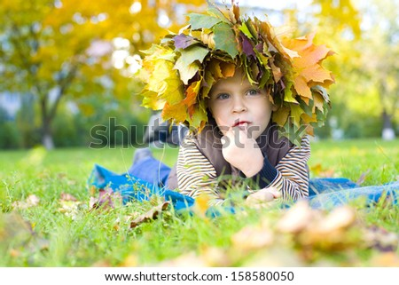 Four-year boy lying on the grass in a wreath of autumn leaves - stock photo