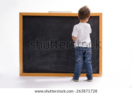 four year old boy draws with chalk on the blackboard - stock photo