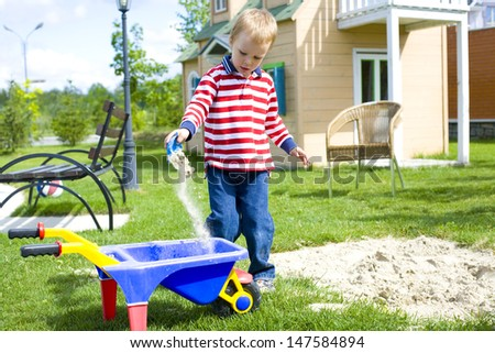 four-year-old boy playing at a playground with sand outdoor - stock photo