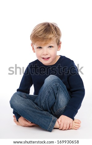 Four year old boy sitting cross legged. Studio Shot on white background.