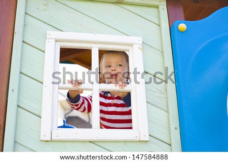 four-year-old boy who is looking out in a window of a children's lodge - stock photo