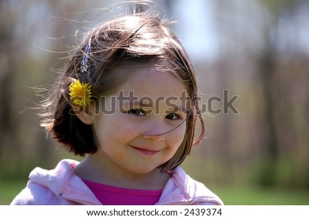 Four year old girl at the park with a dandelion tucked in her hair.